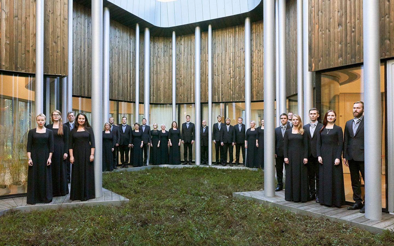 The Estonian Philharmonic Chamber Choir standing between the pillars of a building