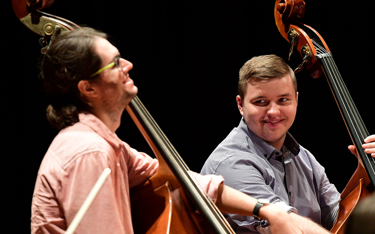 A school student being mentored on the double bass