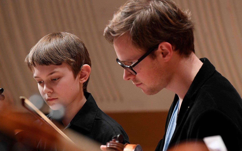 An ACO musician mentoring a young strings player