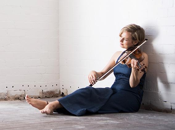 Satu Vänskä sitting on the ground playing a Stradivarius violin